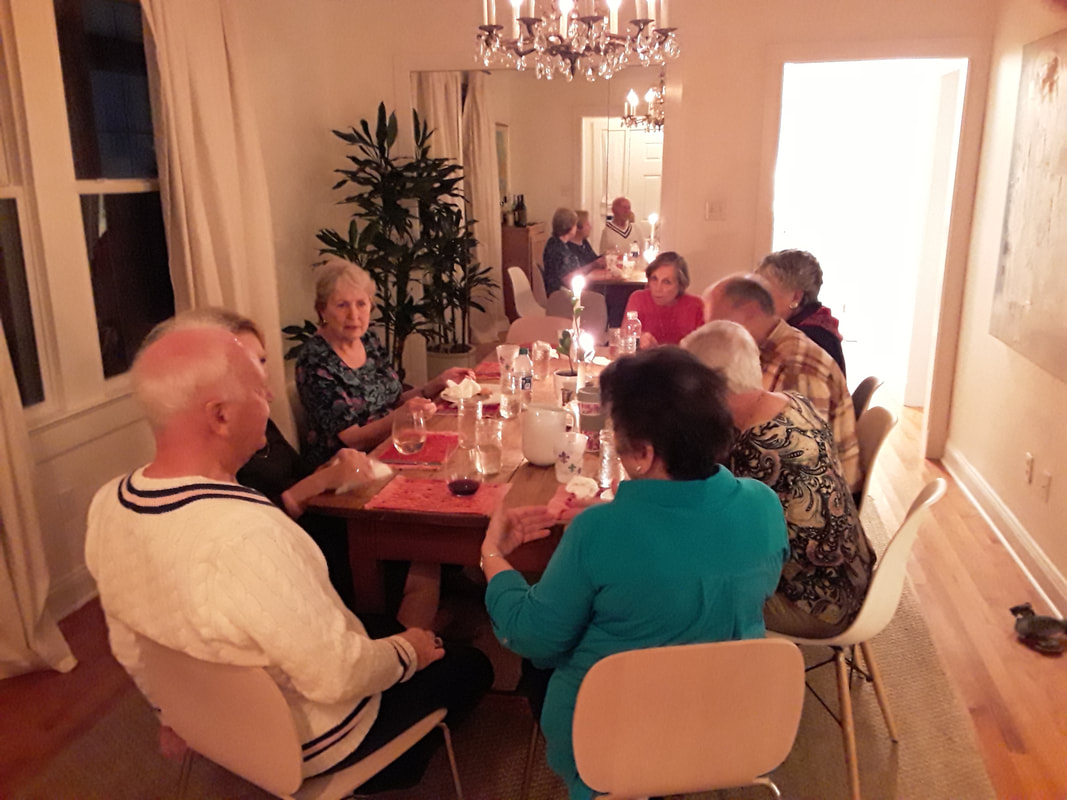 People sitting around tables with candlelight, sharing a meal.