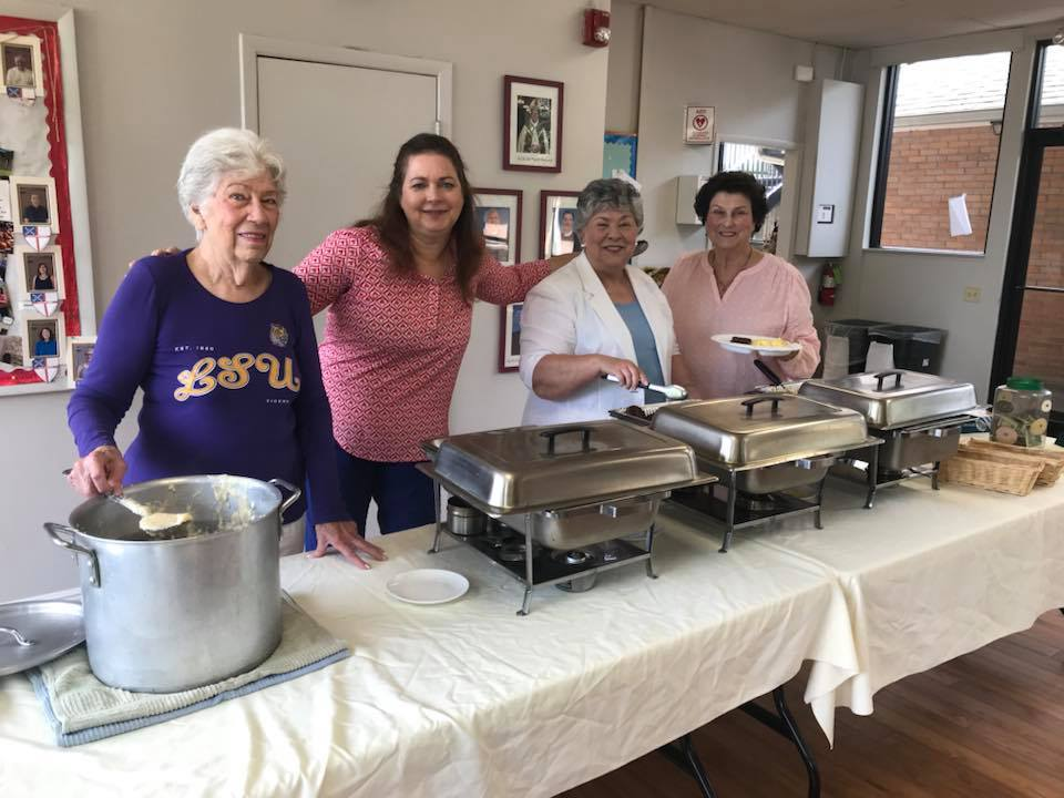 Women standing behind a long table, serving breakfast to other parishioners.